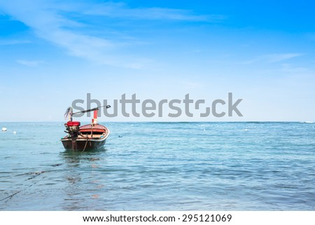 Small wooden fishing boat in blue sea