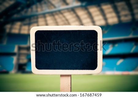 Small wooden framed blackboard on soccer field background  - stock photo