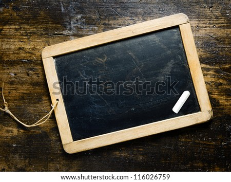 Small wooden framed blank blackboard with a piece chalk on a darl timber background with woodgrain suitable for your greeting, message or menu - stock photo
