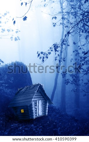 Small wooden house and mysterious landscape of foggy forest  - stock photo