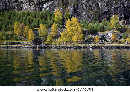Small wooden house in the lake shores - stock photo