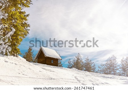 Small wooden house on he mountain covered with snow, Direct sunlight with lens flare from the right side of the frame. Copy space, toned image - stock photo