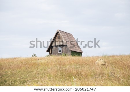 Small wooden house on the hill - stock photo