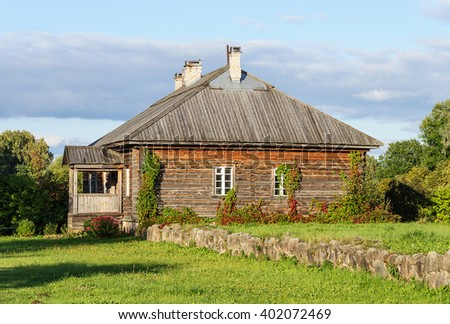 Small wooden house with a lawn and trees around it, summer evening - stock photo