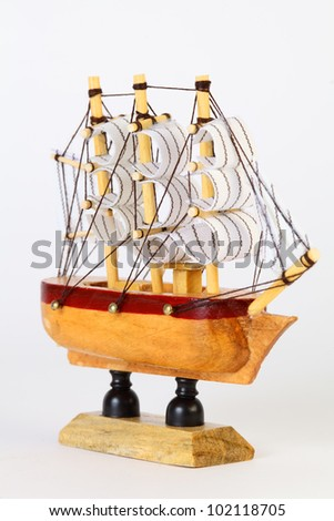 Small wooden model of sailing ship with rigging and white sails on stand - stock photo
