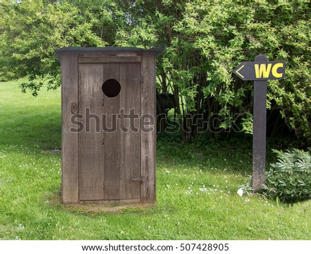 Small wooden outdoors toilet in nature. Directional signs pointing to old rustic cabin toilets. Toilet booth on the countryside. Simple farmhouses latrine on the meadow by the forest.