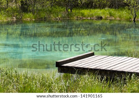 Small wooden pier by the lake. - stock photo