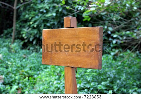 small wooden plaque against a green background - insert your text