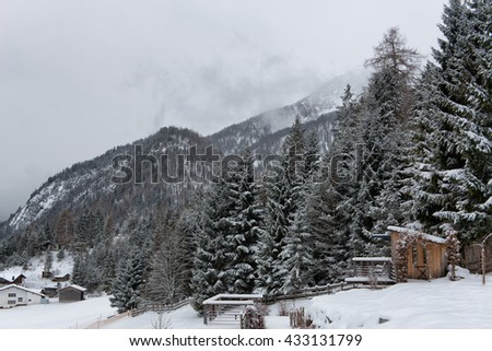 Small Wooden Rural Farm Shack at Edge of Thick Evergreen Forest on Snow Covered Mountainside with Alp Peaks in Background on Overcast Day - stock photo