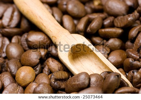 Small wooden scoop among coffee beans - stock photo