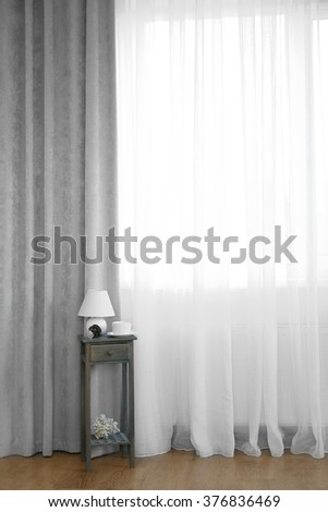 Small wooden table with lamp and cup on curtain background