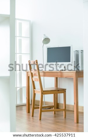 Small wooden table with white computer on it in the corner of room with wooden floor - stock photo