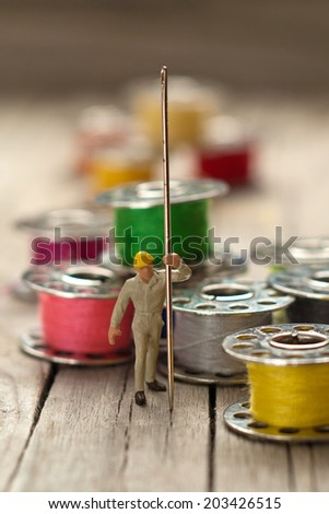 Small worker prepares the material for sewing. Tailoring concept.  - stock photo