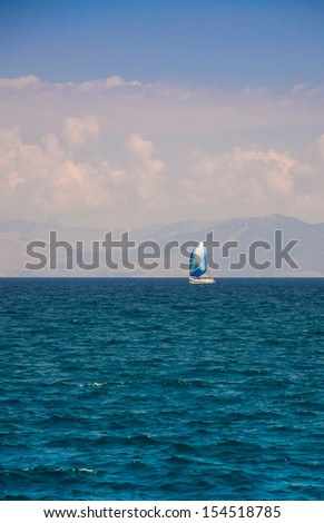 Small yacht in the blue sea off the coast with beautiful clouds - stock photo