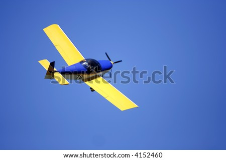 small yellow airplane isolated on blue sky