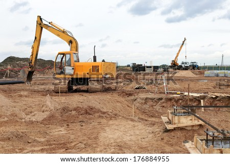 small yellow excavator on a construction site - stock photo