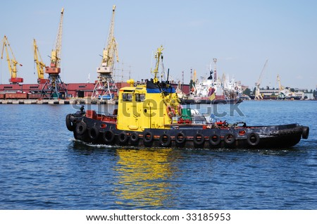 Small yellow towboat against the busy industrial port