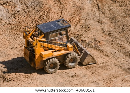 small yellow tractor at work - stock photo