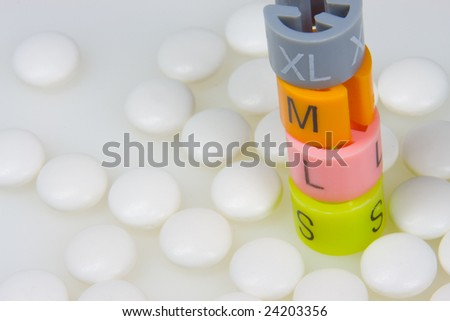 Smaller clothing size by taking pills and drugs - stock photo