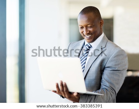 smart african business man using laptop in office - stock photo
