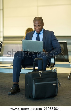 smart african businessman using tablet computer at airport - stock photo
