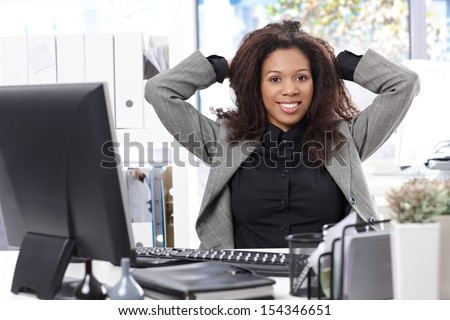 Smart afro businesswoman sitting at desk, smiling, hand in hair. - stock photo