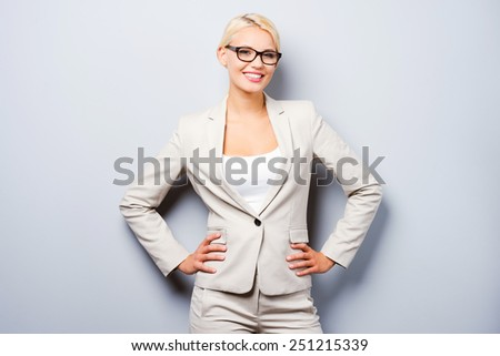 Smart and beautiful. Confident young businesswoman holding hands on hips and looking at camera while standing against grey background - stock photo