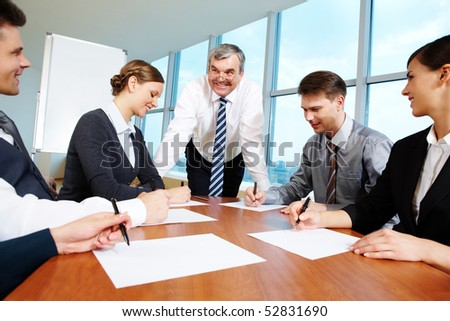 Smart and confident boss looking at managers writing on papers at meeting - stock photo