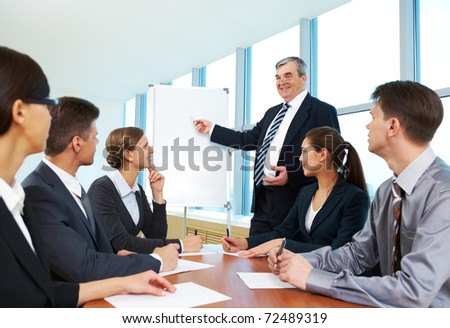 Smart and confident boss pointing at whiteboard and looking at managers during presentation - stock photo