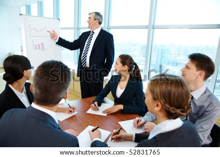 Smart and confident boss pointing at whiteboard while making presentation - stock photo