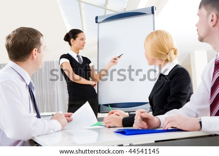 Smart and confident employee pointing at whiteboard while presenting her ideas - stock photo
