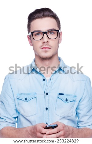Smart and confident. Handsome young man in shirt looking at camera and holding mobile phone  while standing against white background  - stock photo
