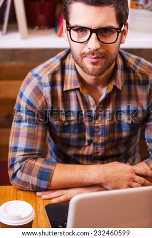 Smart and confident. Top view of confident young man looking at camera while sitting at the desk with laptop and coffee cup on it  - stock photo