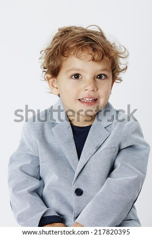 Smart and smiling young boy in suit jacket, portrait
