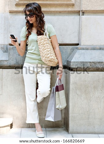 Smart and young consumer woman leaning on a grand stone building wall, holding paper shopping bags and using a smartphone during a shopping spending day, outdoors. - stock photo