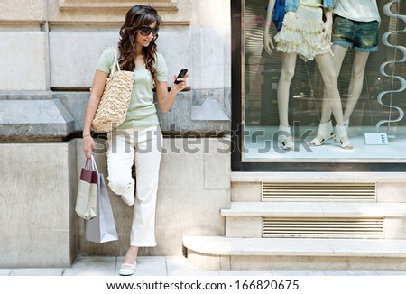 Smart and young consumer woman standing by a fashion store window display with manikins, holding paper shopping bags and using a smartphone during a sunny day, outdoors.