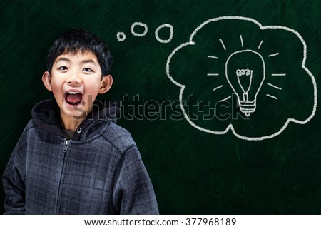 Smart Asian boy with smart idea in classroom setting and chalkboard background. - stock photo