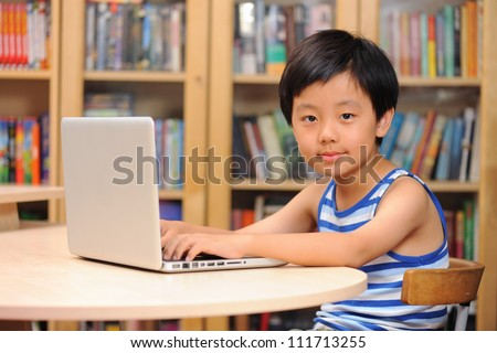 Smart Asian boy working on a laptop computer - stock photo