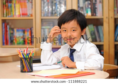 Smart Asian schoolboy wearing white shirt and tie sitting at a desk and holding a pencil - stock photo
