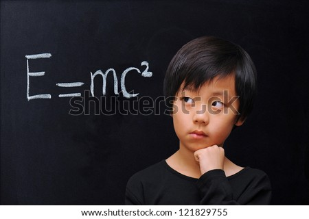 Smart boy in front of blackboard with physics formula - stock photo