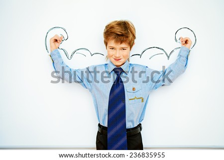 Smart boy stands by the whiteboard in a classroom expressing the power of knowledge. Educational concept. Copy space. - stock photo