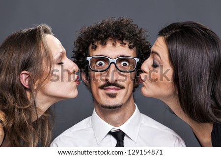 Smart boy take two kisses from tow different girls - stock photo