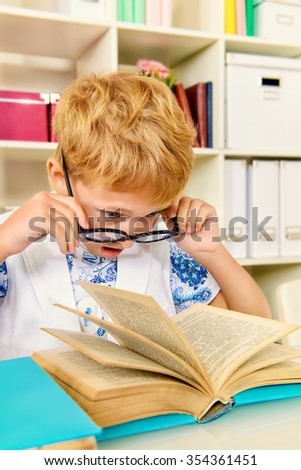 Smart boy wearing glasses sitting at the desk and looking at the camera with surprise. Education.  - stock photo