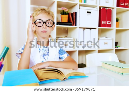 Smart boy wearing glasses sitting at the desk and raises his hand. Education.