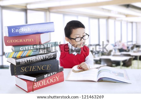 Smart boy with glasses study different literature in the library - stock photo