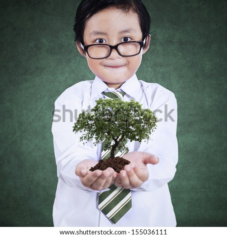 Smart boy with green plant on the classroom - stock photo