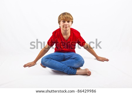 smart boy with red shirt sitting in tailor seat at the floor