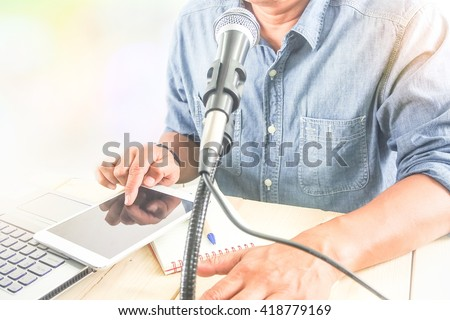 smart business man using microphone for public speaking seminar conference tablet computer ,selective focus at top of microphone - stock photo