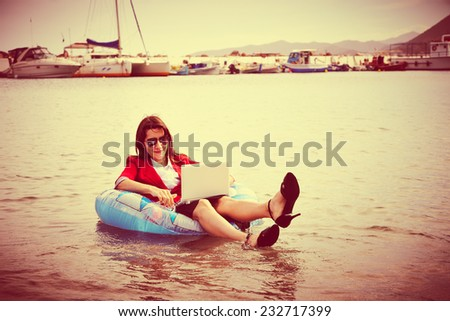 Smart business woman floating in the sea  and working on laptop