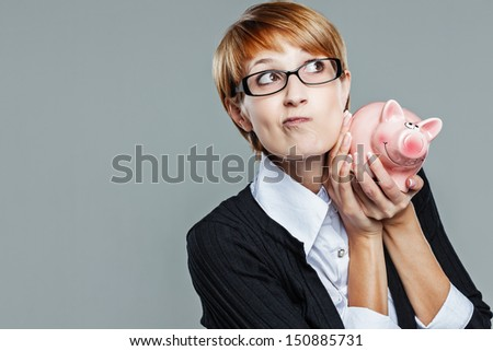 Smart business woman questioning her piggy bank isolated on grey - stock photo